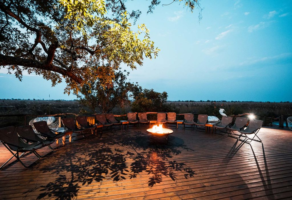 Chairs around the bonfire in Botswana, Africa. An owl and African sunsets