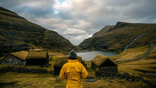 David Simpson and houses with turf roof at Saksun in Faroe Islands. The gem of the Faroe Islands