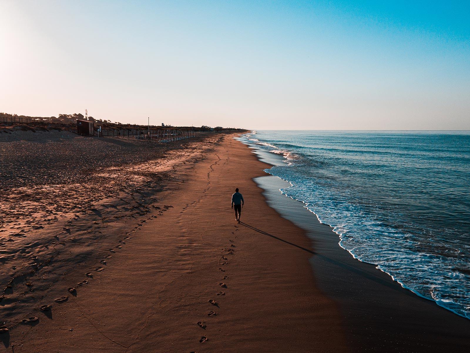 DAVID SIMPSON WALKING DOWN A QUIET BEACH IN PORTUGAL ALONE AT SUNRISE
