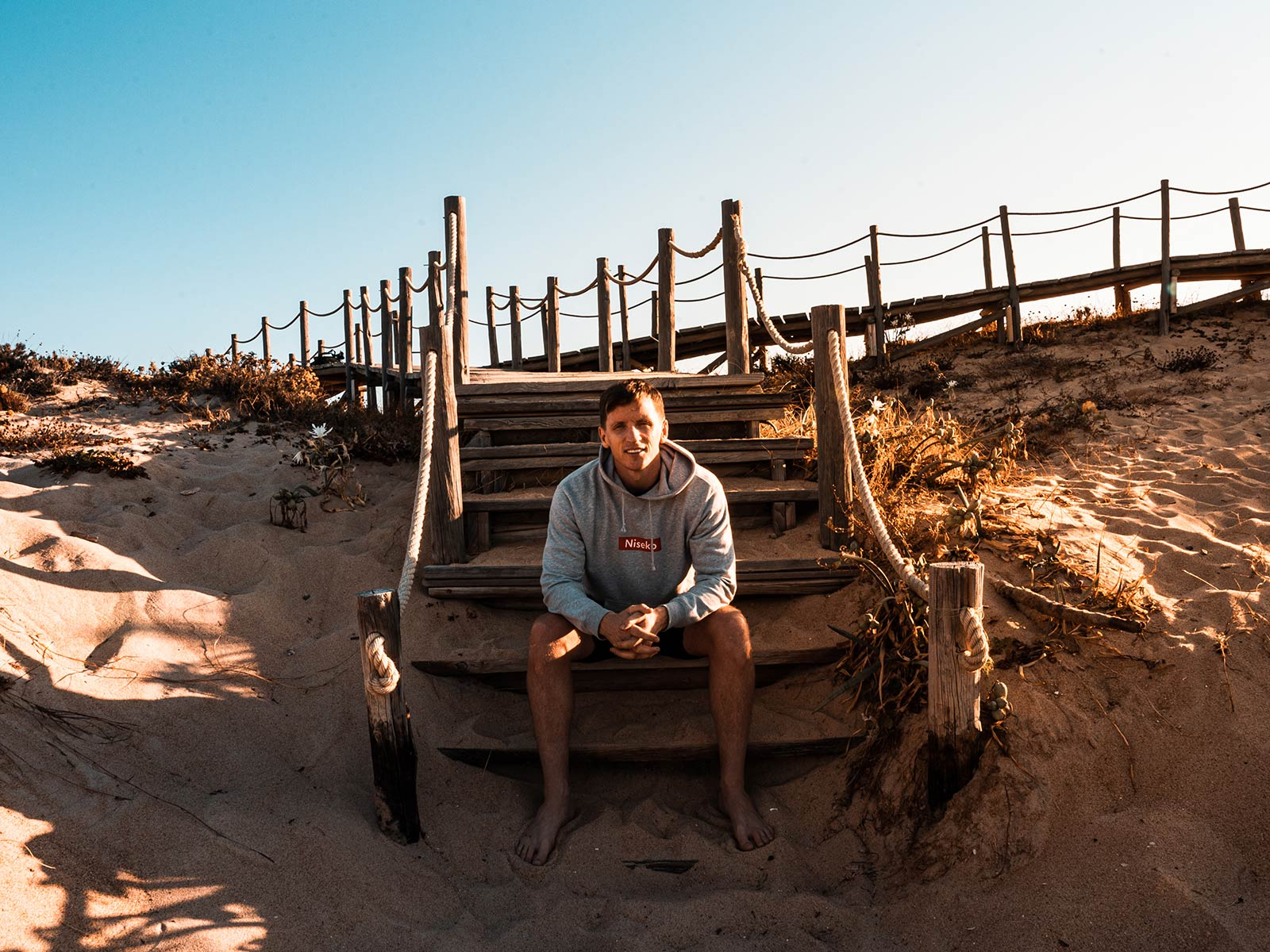 PORTRAIT IMAGE OF DAVID SIMPSON SITTING ON STEPS AT BEACH IN PORTUGAL